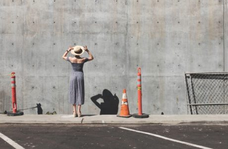 Woman in a dress in front of a concrete wall by Charlee Deets on Unsplash