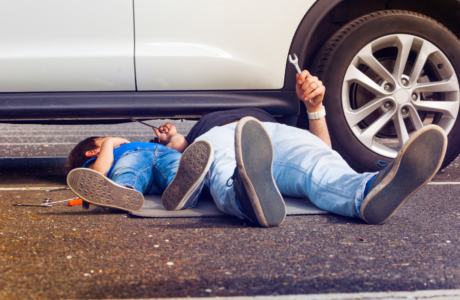 Father and son working under broken car together. source: istockphoto