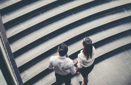 Businessman and Business woman go up the stairs
